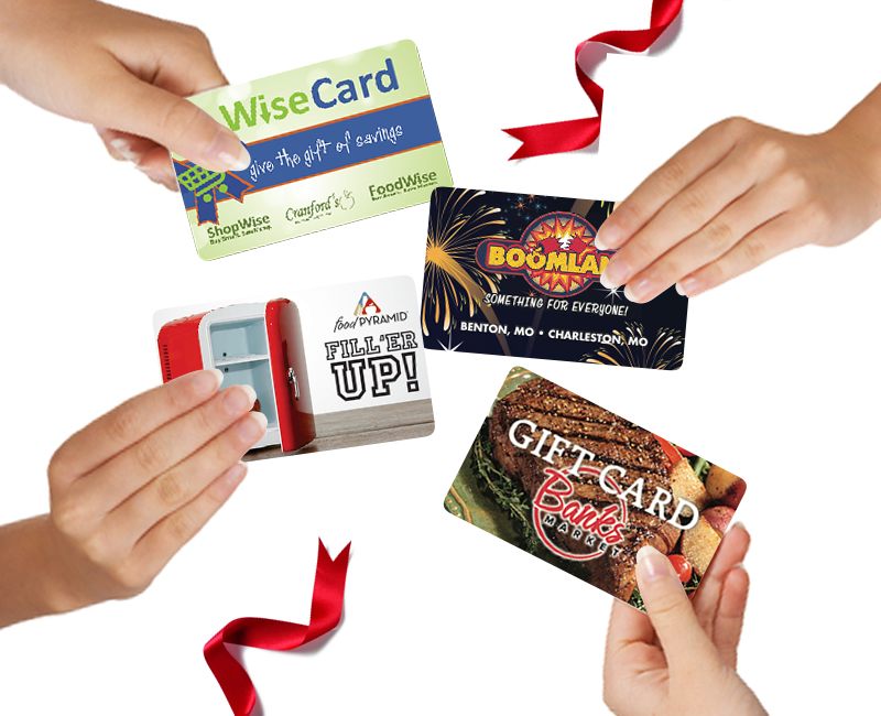 Close up of hands holding 4 different store gift cards.