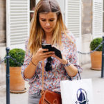 Woman Holding Purse and Shopping Bag on Smartphone