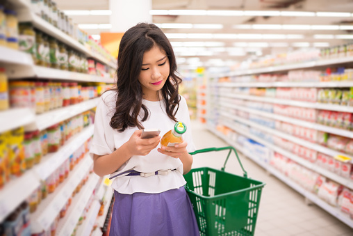 Woman in grocery store holding phone and juice looking at juice label.