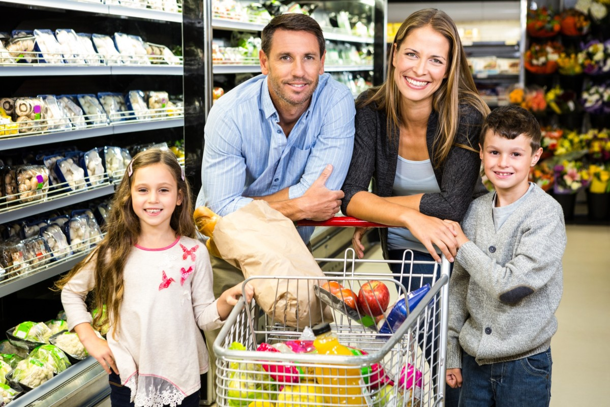 Family leaning on grocery cart in store.