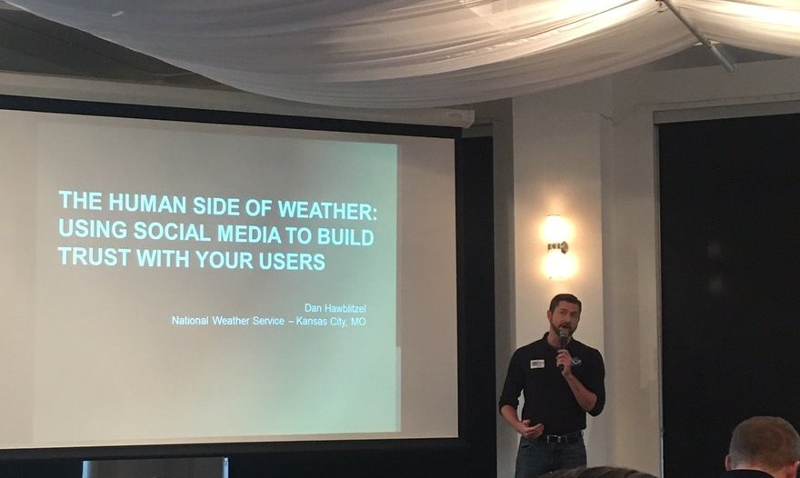 Man in front of screen that says The Human Side of Weather: Using Social Media to Build Trust with your Users