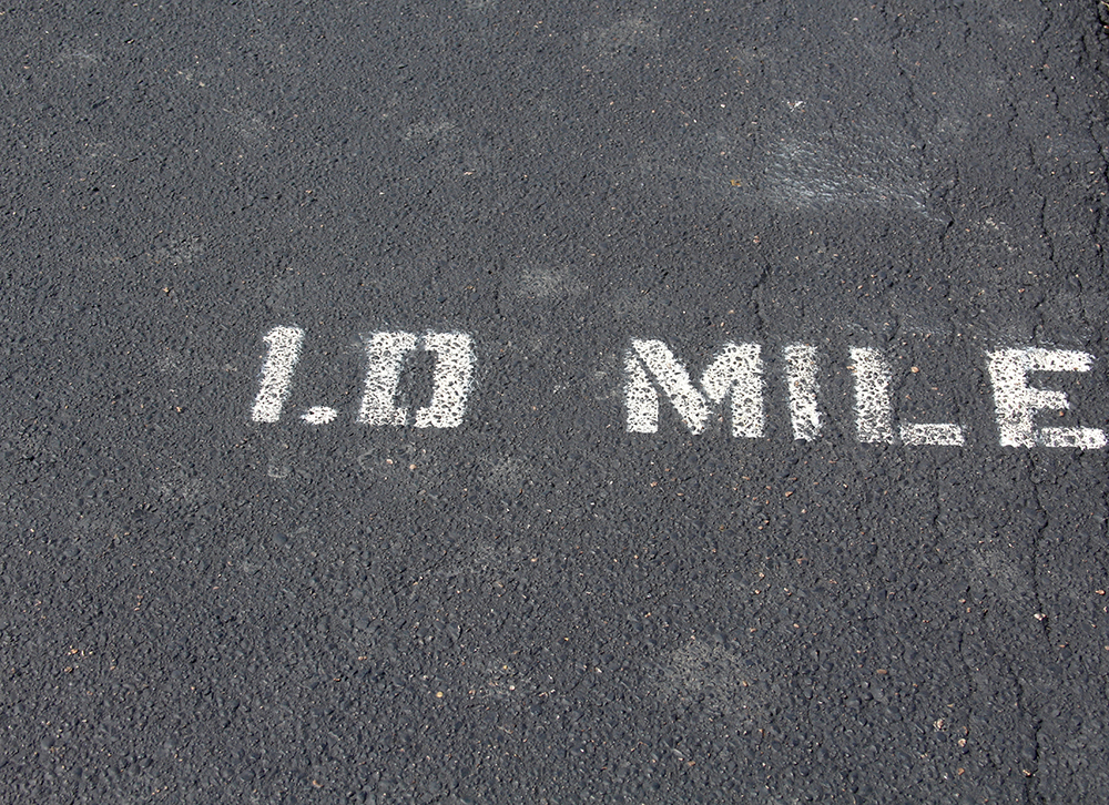 The mile marker painted white on the blacktop of the footpath on a close up view.